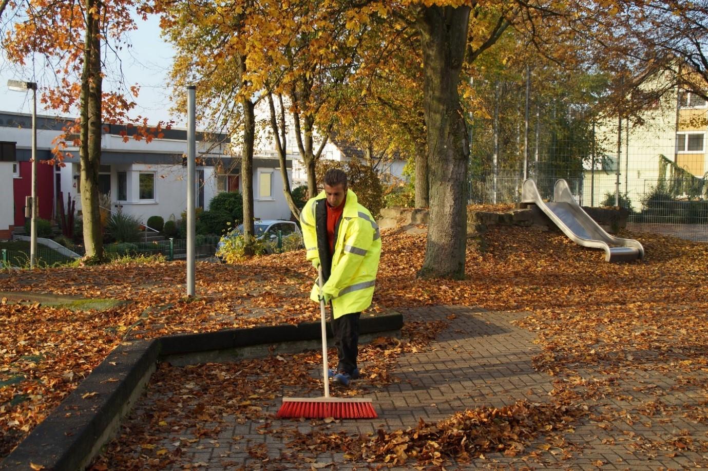 Ehrenamtlicher Helfer fegt Herbstlaub